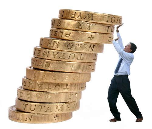 Geschäftsmann drückt Münzen nach oben, um sie vom Herabfall zu stützen
