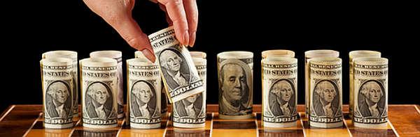 Money strategies concept - dollar bills on chess board