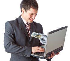 Man receives money from hand within laptop screen / Mann bekommt Geld von einer Hand aus einem Laptop