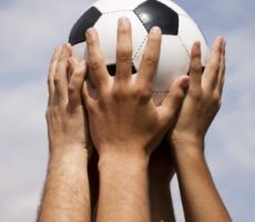 Hands clasped around a ball emulating the FIFA World Cup Trophy