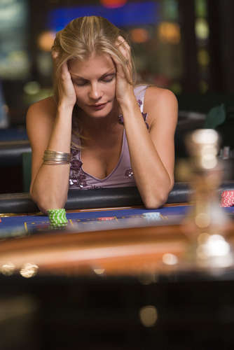 Young attractive lady in depression at roulette table