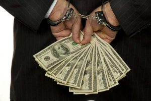 Handcuffed businessman with bank notes