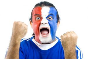 French football fan with face painted in the colours of the French flag