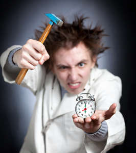 Crazy young scientist trying to break his alarm clock