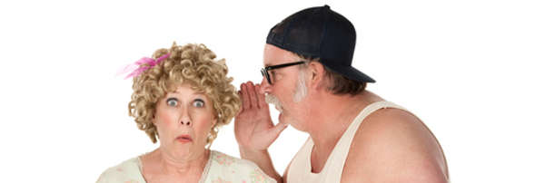Bespectacled, bearded man whispers in the ear of his surprised wife