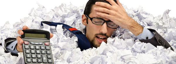 Man with calculator sunk into a heap of paper
