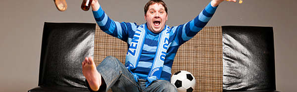 Soccer fan sitting on sofa with beer at home