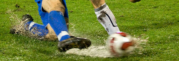 Football players legs close shot with ball
