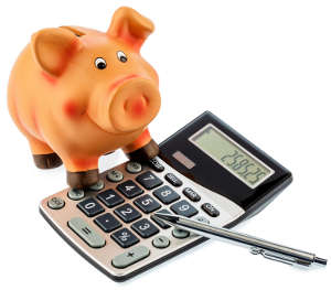 Red pen on a calculator beside a piggy bank - save on costs, expenses, and budget