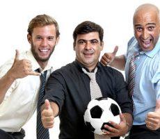 Team of happy businessmen cheering and embracing a soccer ball / Team von fröhlicher Geschäftsleute mit Fußball