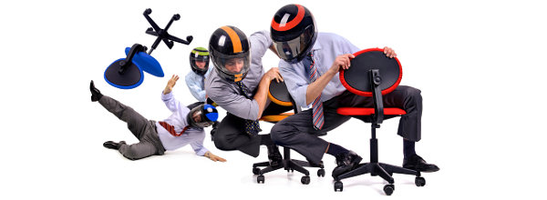 Businessmen with helmets racing in office chairs