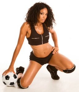 Sexy female couch squatting with football ball by her legs