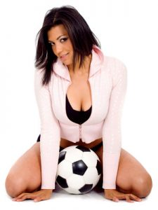 Fashion girl in a sexy position with a soccer ball