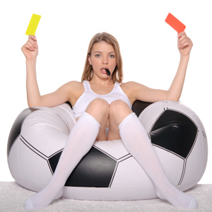 Sexy female sitting on a large football with red and yellow cards