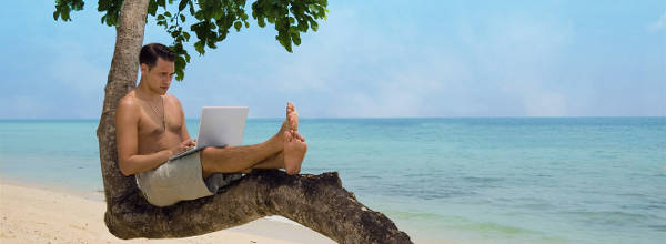 Attractive man with laptop seated in a tree on a tropical beach